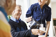 Midsection of happy female caretaker serving black coffee to senior man at nursing home - MASF04902