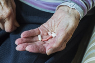 Midsection of senior woman holding pills while sitting at home - MASF04911