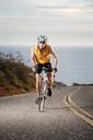 Man cycling on road against sea - CAVF42161