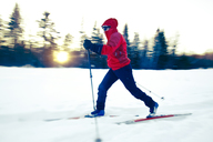 Full length of skiier skiing on snow covered field by bare trees - CAVF42218