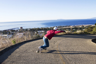 Rear view of man longboard skating on road in town by sea against clear sky - CAVF42257