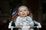 Cute baby girl with messy face looking away while sitting on high chair at home - CAVF42323