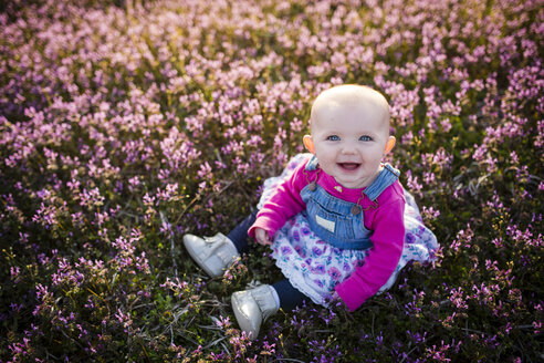 High angle portrait of happy baby girl sitting on field - CAVF42332