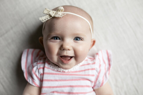 Close-up portrait of happy baby girl relaxing on bed at home - CAVF42353