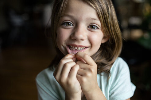 Portrait of happy girl showing tooth gap at home - CAVF42374