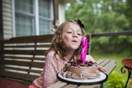 Girl blowing out number 6 candle on birthday cake at porch - CAVF42380