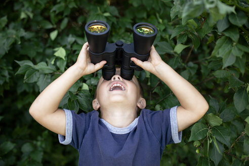 Playful boy looking through binoculars while standing against plants - CAVF42413