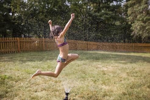 Cheerful girl jumping over sprinkler at yard - CAVF42467