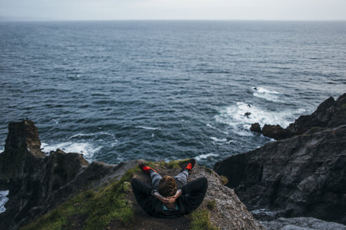 High angle view of hiker sitting with hands behind head on cliff against seascape - CAVF42482