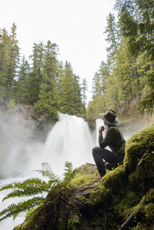 Side view of female hiker looking at waterfall while sitting on mossy rock - CAVF42503