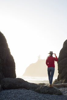 Rear view of hiker standing at Ruby Beach against clear sky - CAVF42512