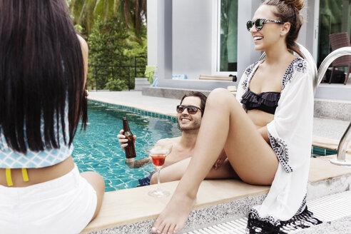 Cheerful friends enjoying vacation at poolside - CAVF42695