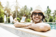 Happy man relaxing in swimming pool at tourist resort - CAVF42716