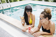 Cheerful women having drinks in swimming pool - CAVF42725