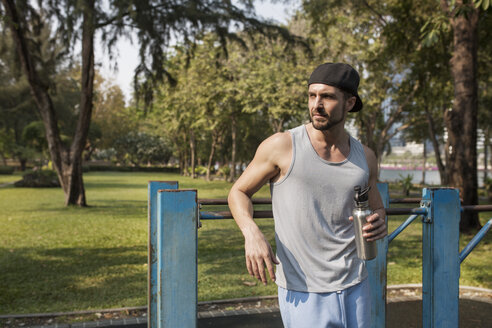 Man holding water bottle after exercising at park - CAVF42737