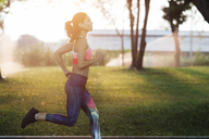 Side view of woman jogging at park on sunny day - CAVF42764