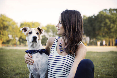 Loving woman sitting with dog on grassy field at park - CAVF42869