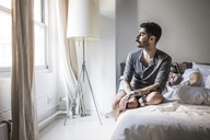 Gay man looking away while partner sleeping on bed - CAVF43001