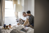 Gay men reading newspaper while sitting on bed at home - CAVF43007