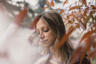 Portrait of young woman in between autumn leaves - AFVF00438