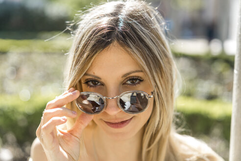 Portrait of smiling young woman with mirrored sunglasses - AFVF00444