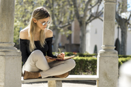 Young woman with notebook sitting on bench writing down something - AFVF00447
