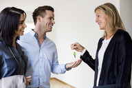 Happy real estate agent giving keys to couple in new house - MASF04927