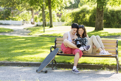 Happy loving couple looking photos on camera while sitting on bench in park - MASF04942