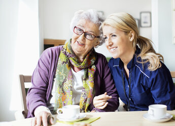 Happy female caretaker and senior woman looking away while sitting at table in nursing home - MASF04945