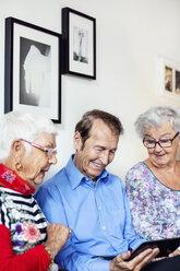 Happy senior people using digital tablet at nursing home - MASF04951