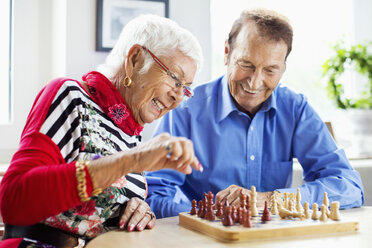 Happy senior couple playing chess at table in nursing home - MASF04954
