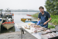 Happy fisherman cleaning fish at table by lake - MASF04972