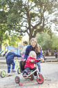 Happy teacher assisting girl to ride tricycle on playground - MASF04984