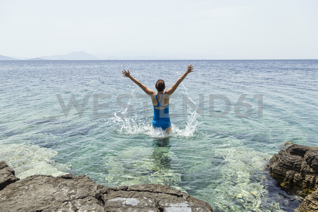 Greece, Lefokastro, woman jumping into water, raised arms - MAMF00061