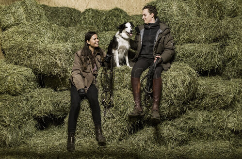 Full length rear view of happy young couple with dog sitting on hay stack in stable - MASF04994