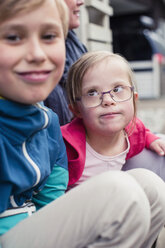 Girl with down syndrome looking at brother outdoors - MASF05000