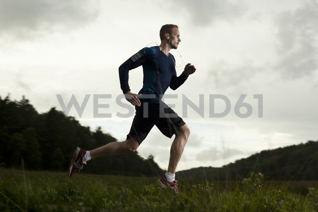 Full length side view of determined man running on grassy field against cloud sky - MASF05012