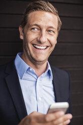 Happy businessman using smart phone - MASF05021