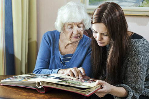 Grandmother and granddaughter looking at photo album in house - MASF05030