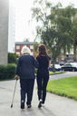 Full length rear view of elderly woman walking with granddaughter on footpath - MASF05033