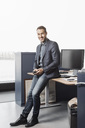 Full length portrait of confident businessman leaning on desk in office - MASF05039