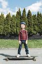 Full length portrait of happy boy standing on skateboard against trees - MASF05042