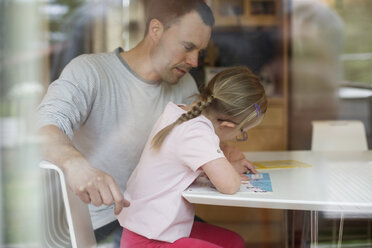Father assisting handicapped girl in studies at table - MASF05049