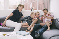 Family using smart phone on sofa at home - MASF05058