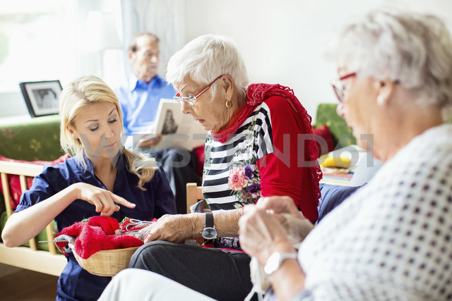 Female caretaker assisting senior women in knitting while man reading book in background at nursing home - MASF05067