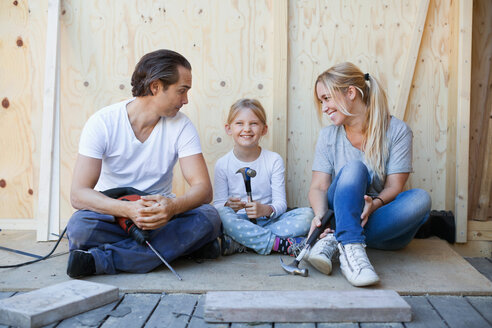 Family sitting on porch of house being renovated - MASF05073