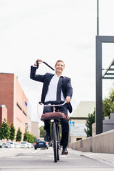 Full length of happy businessman removing tie while riding bicycle on city street - MASF05100