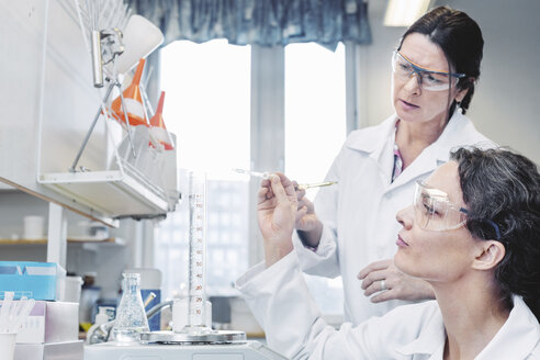 Female scientists analyzing chemical in laboratory - MASF05115