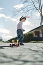 Full length of boy pulling toy car on footpath at yard - MASF05121