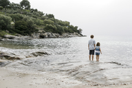 Greece, Chalkidiki, back view of brother and little sister standing at seaside - KMKF00160